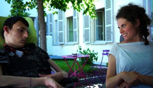 Due persone che chiacchierano sedute a un tavolo