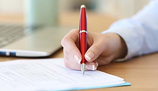 inquadratura di una mano con la penna che firma dei documenti