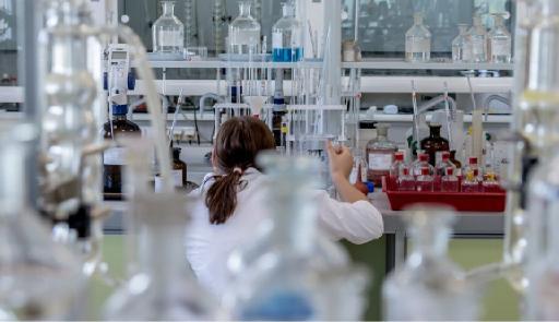 Immagine di una ricercatrice di spalle all'interno di un laboratorio scientifico
