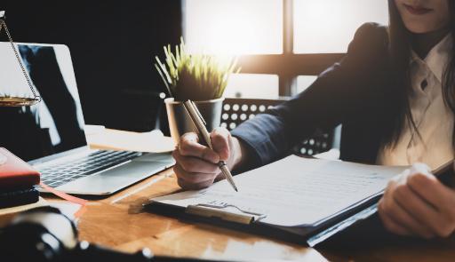 donna seduta ad una scrivania, scrive su un blocco di fogli, accanto a lei un pc portatile