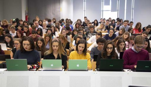 Aula piena di studenti con laptop aperti sui banchi