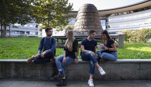 Studenti e studentesse seduti su di un muretto intenti a chiaccherare