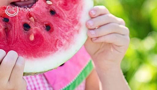 Una bambina addenta una fetta di anguria