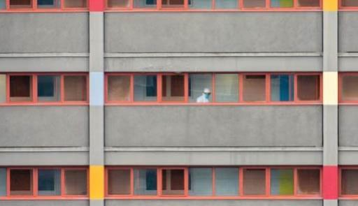 Visuale di un condominio dall'esterno con una persona in tuta anticontagio su di un balcone