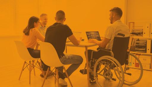 persone, di cui una sulla sedia a rotelle, sedute intorno ad un tavolo