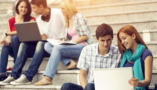 Studenti seduti sulle scale che guardano il computer