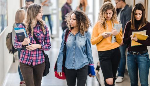 Studentesse chiacchierano camminando nella hall di un campus
