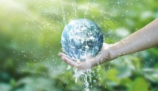 Un piccolo pianeta Terra poggia su una mano grondante acqua