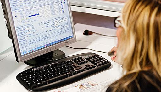 Una donna seduta a una scrivania con di fronte il monitor di un pc