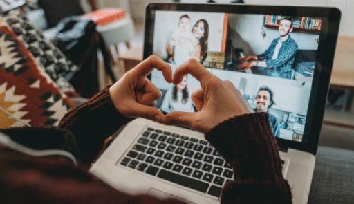 Una persona fa il segno del cuore con le mani con di fronte uno schermo e i visi di altre persone in videochiamata