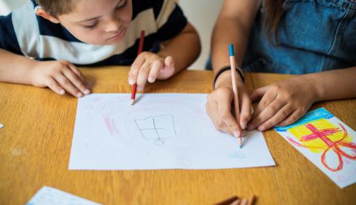 fotografia di un bambino che lavora con un adulto ad un disegno