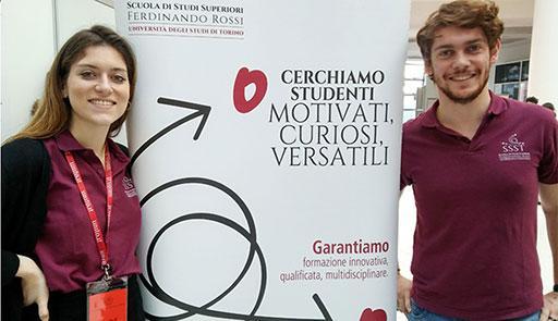 Un ragazzo e una ragazza sorridono di fianco al totem della Scuola Ferdinando rossi