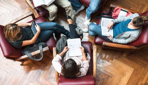 foto dall'alto di alcuni studenti seduti su delle poltroncine disposte in circolo