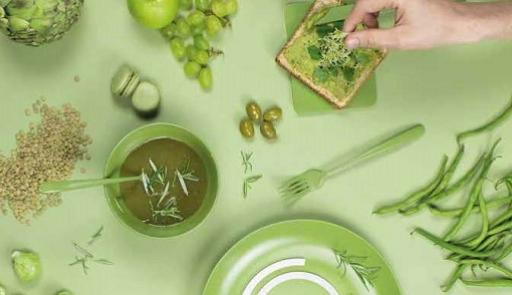 sfondo colorato e mano maschile che compone un sandwich con verdure