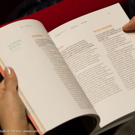Uno spettatore sfoglia il documento Rapporto di sostenibilità 2013-2014