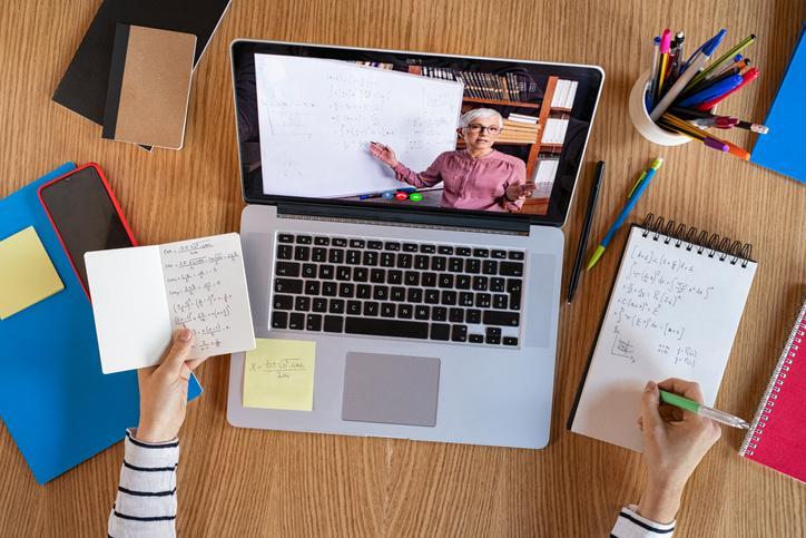 Immagine con computer portatile sul tavolo accesso con videolezione a distanza. Intorno al computer sono poggiati telefono cellulare, block notes, libri e portabiro. Si intravvedono le mani di una studentessa che reggono sulla mano sinistra un block notes con appunti e sulla mano destra una biro che prende appunti su un altro block notes