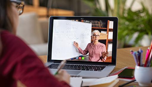 Studentessa al computer e sul display la docente che tiene una lezione online