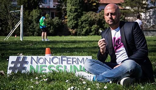 Foto di Luca Abete seduto su prato con un fiore in mano, di fianco è presente un cartello con la scritta:#NonCiFermaNessuno