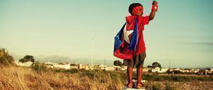 Bambino di colore con il mantello di Capitan America in un paesaggio africano