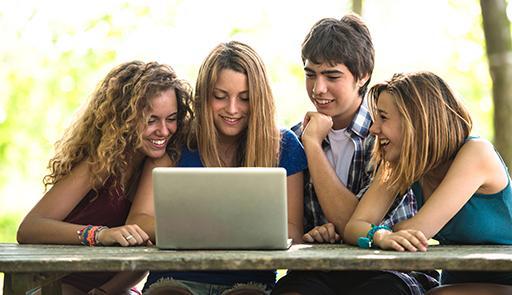 Gruppo di studenti seduti ad un tavolo intorno ad un computer