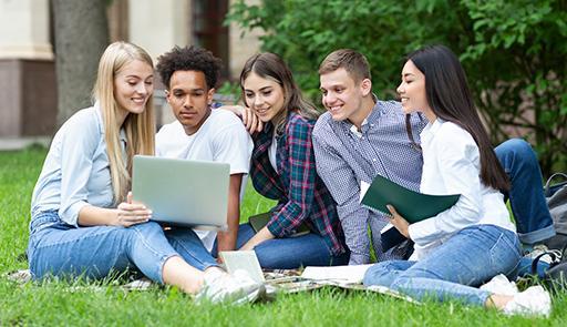 Gruppo di studenti seduti su un prato intorno ad un computer