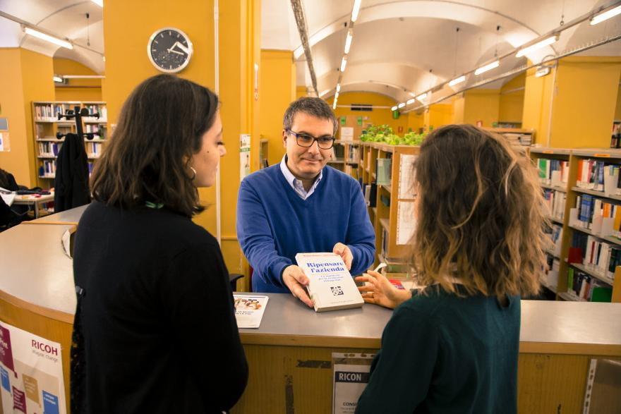 Bibliotecario che porge un libro a due studentesse