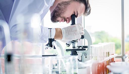 Ricercatore al microscopio all'interno di un laboratorio