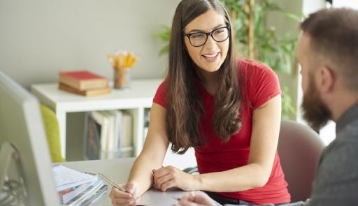 Immagine di una studentessa sorridente con le mani poggiate su una scrivania che regge in mano una biro e di uno studente di profilo intento ad ascoltare