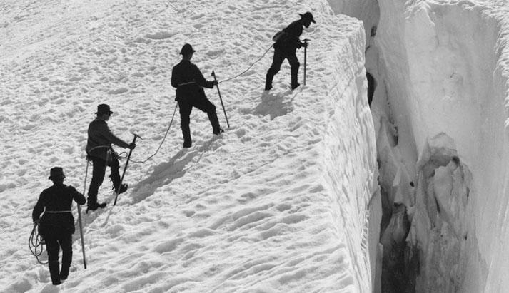 Foto in bianco e nero di 4 alpini a bordo di un crepaccio
