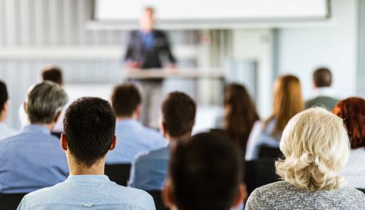 foto di alcune persone sedute, riprese di spalle, che ascoltano una persona che parla al podio