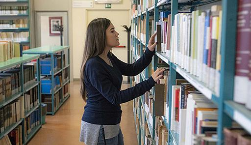 ragazza in cerca un libro in uno scaffale di una biblioteca