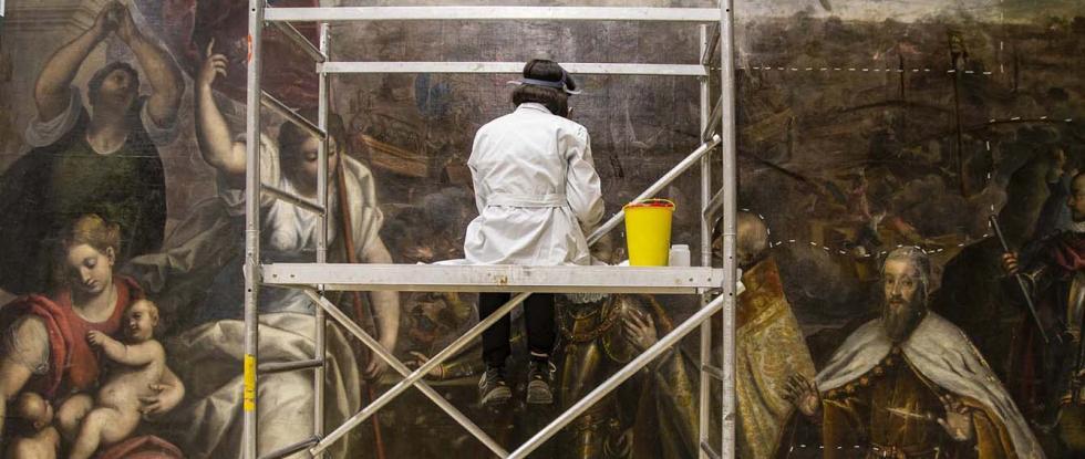 Ricercatrice intenta al restauro di un quadro