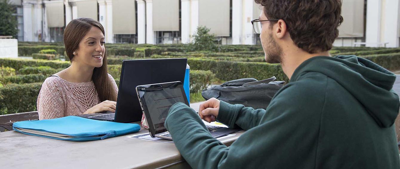 Due studenti impegnati nello studio su di un tavolo all'aperto