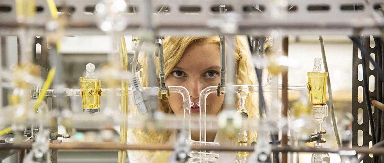 Ricercatrice in laboratorio dietro a una serie di ampolle trasparenti