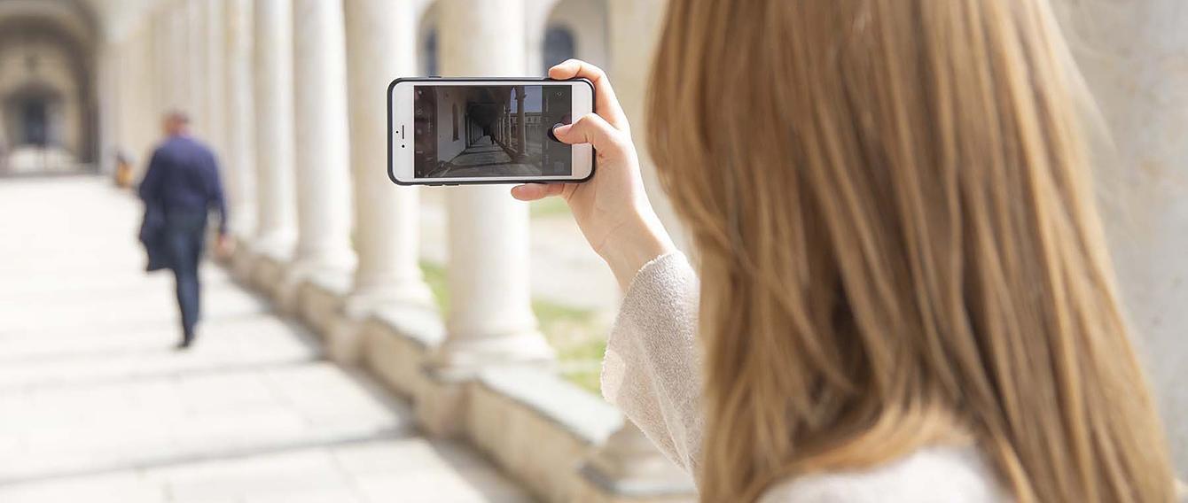 Giovane donna inquadra con lo smartphone il corridoio della sedi di Savigliano