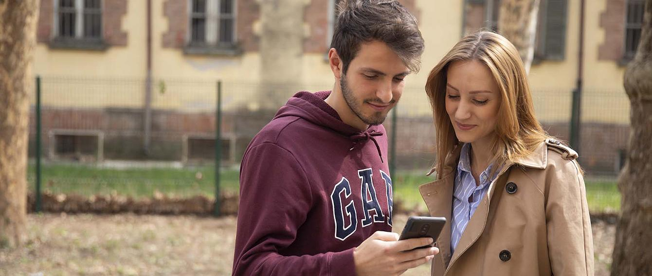 Un ragazzo e una ragazza in un parco guardano il cellulare