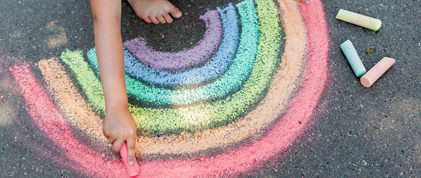 Mano di bambino che con un gessetto disegna un arcobaleno per terra
