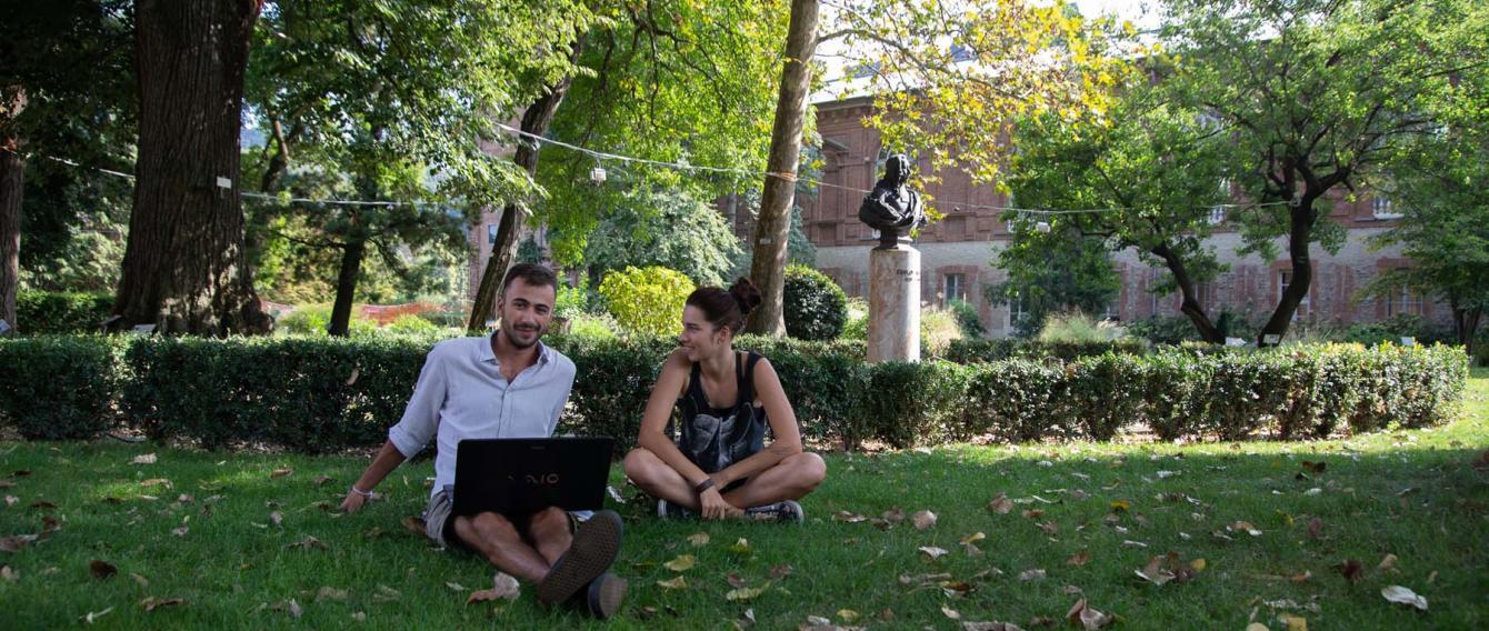 Un ragazzo con un portatile è seduta sul prato dell'orto botanico con accanto una ragazza che sorride