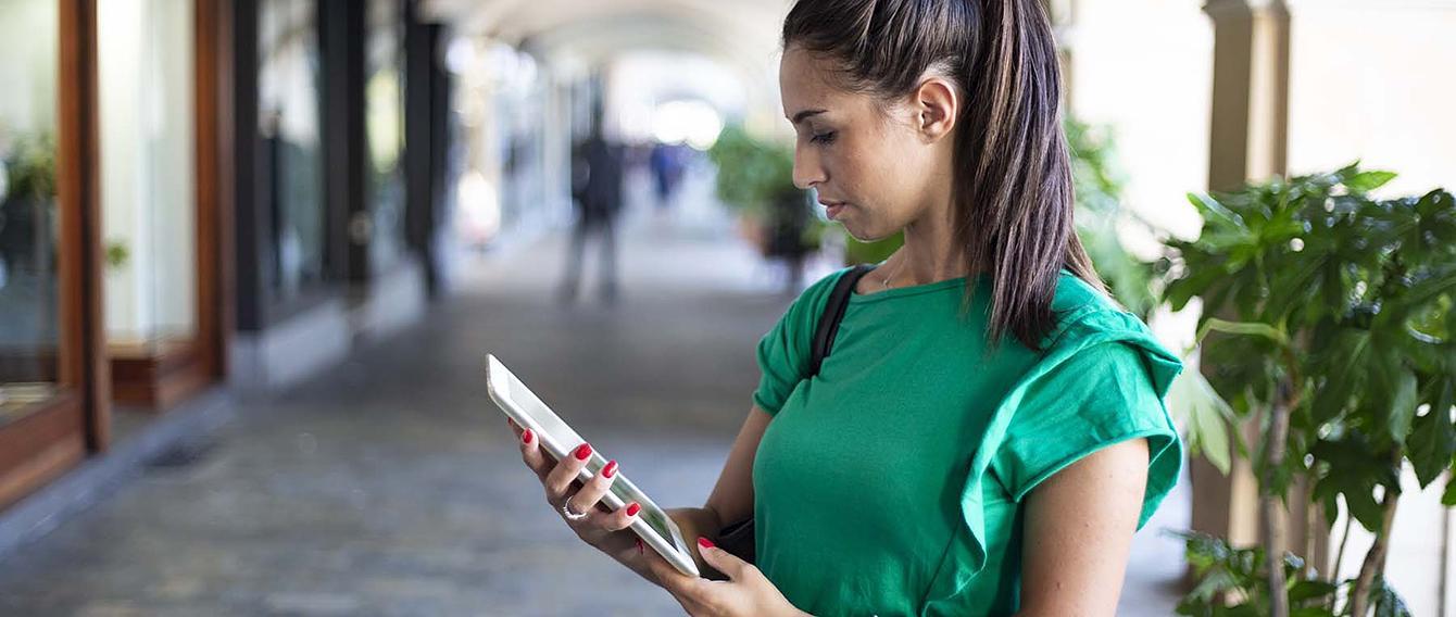 Studentessa che consulta un tablet sotto i portici di Savigliano