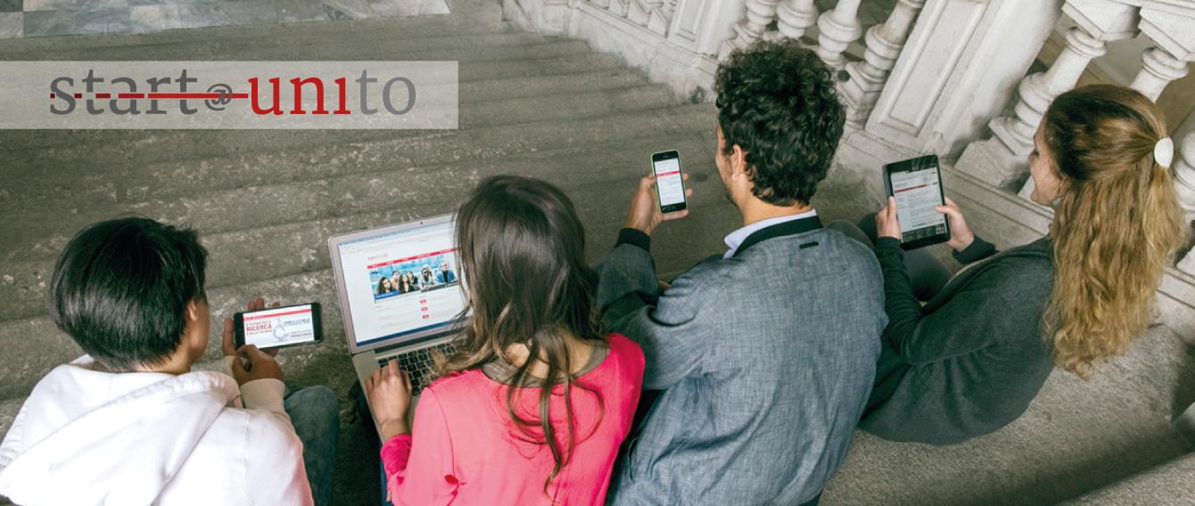 Ragazzi seduti sulle scale del loggiato che consultano tablet e telefonini