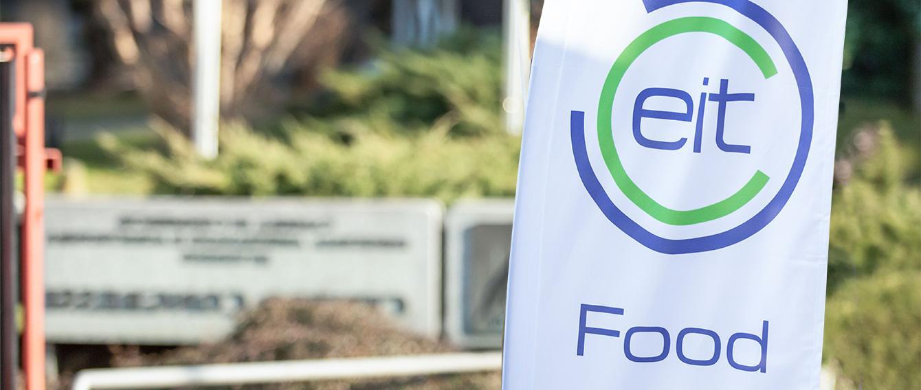 Bandiera bianca con logo EIT Food, prato sullo sfondo