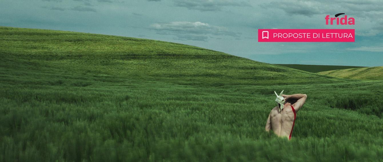 uomo a torso nudo, di schiena, con un teschio di animale in mano, immerso in un prato di erba altissima