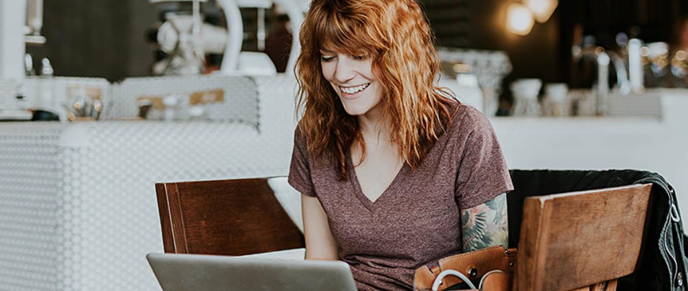 Giovane donna seduta in un locale pubblico che consulta un laptop