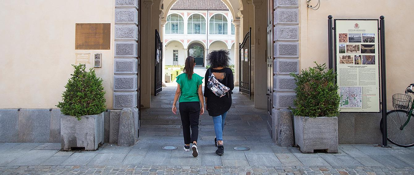 Due giovani donne attraversano un portone aperto